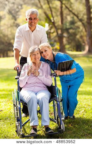 caring nurse hugging senior patient outdoors