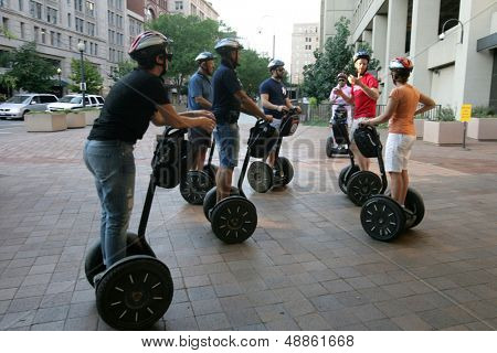 WASHINGTON, DC - JULY 29: Tourists stand on Segways as they listen to a guide during a Segway tour outside the J. Edgar Hoover, FBI headquarters building on July 29, 2013 in Washington.