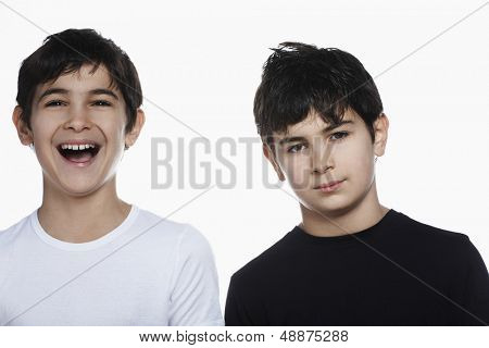 Closeup portrait of confident preadolescent boy with happy brother isolated over white background