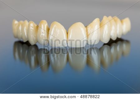 Beautiful ceramic teeth made in the dentist 's office on mirror surface. poster