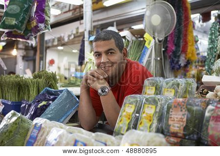 Portrait of confident male grocery store owner smiling while leaning on counter