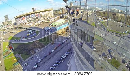 MOSCOW, RUSSIA - OCT 30, 2013: (view from unmanned quadrocopter) Industrial abseiler wash windows of Business Center Diamond Hall, Olympiysky Sports Complex. Business Center Diamond Hall built in 2010