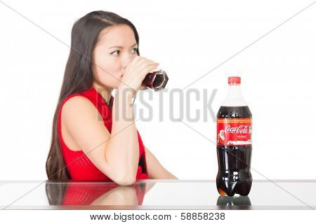 NAKHODKA, RUSSIA - JANUARY 18, 2014: Girl drinks Coca-Cola, on the table a bottle of Coca-Cola. Coca-Cola is a carbonated soft drink sold in stores, restaurants, and vending machines worldwide.