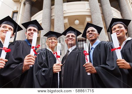 group of multicultural graduates standing outdoors with dean poster