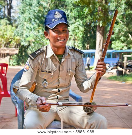 SIEM REAP, CAMBODIA - NOV 21, 2013: Unidentified Policeman play on traditional cambodian musical instrument Thro khmer in Angkor Wat and collect money, on Nov 21, 2013 in Siem Reap, Cambodia.