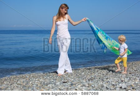 Mother And Child With Shawl Walk On Edge Of Sea