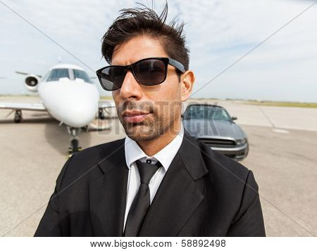 Portrait of confident mid adult businessman in front of car and private jet at terminal