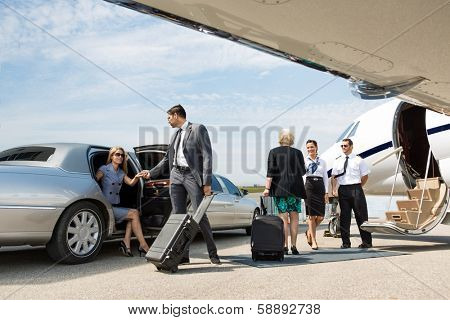 Business partners about to board private jet while airhostess and pilot greeting them