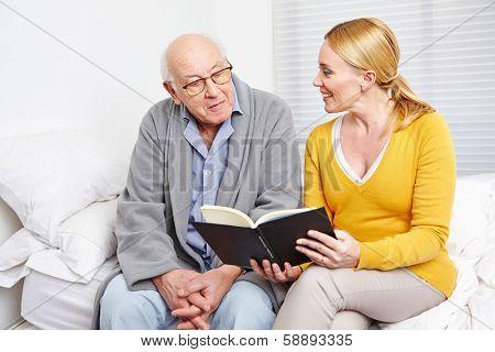 Woman reading a book to a senior citizen man in nursing home