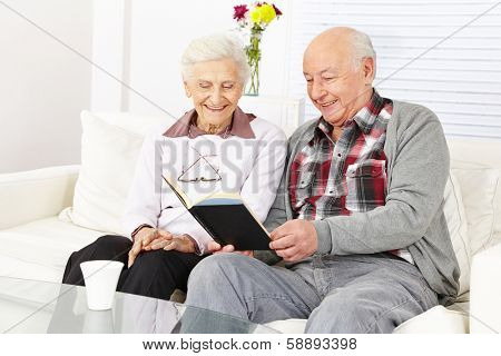 Senior citizen couple reading a book together at home