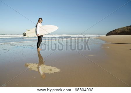 Tenage girl in the beach with her surfboard