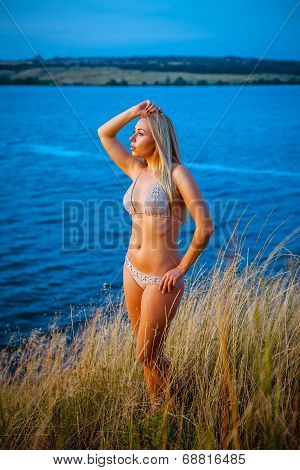 Girl in a bikini looks into the distance. Deep blue water. poster