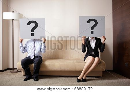Problem in young couple - young couple holding billboard sign with question mark poster