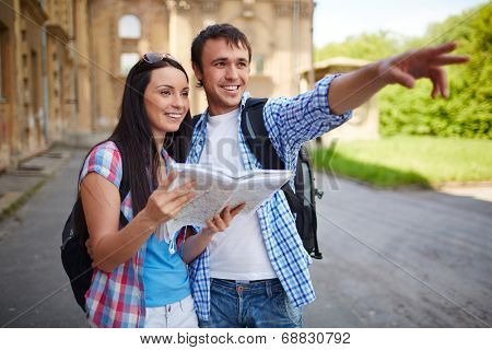 Couple of travelers with map sightseeing in ancient town