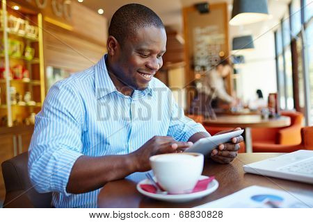 Image of happy young man using digital tablet in cafe