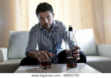 Attractive drunk business man at home sitting on couch at living room wasted holding whiskey bottle in alcoholism problem alcohol abuse and addiction concept looking grunge messy and sick with edgy radical studio lightning poster