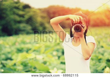 young woman photographer taking photo of blooming lotus at park