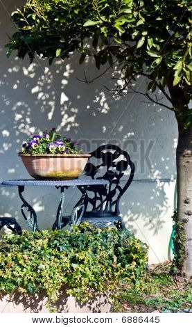 A Garden Table And Chair With Potted Flowers Under A Tree