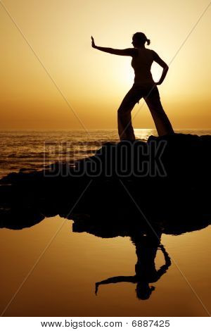 Yoga woman silhouetted against the setting sun with a natural reflection in a rockpool poster