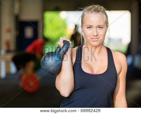Portrait of confident female athlete lifting kettlebell at gym