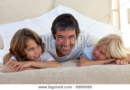 Smiling Father Talking With His Children Lying On Bed