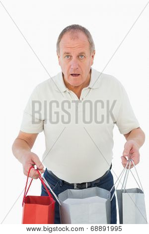 Mature man feeling buyers remorse holding bags on white background