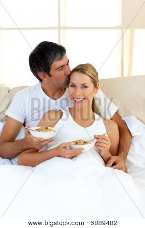 Affectionate Couple Eating Cereals Lying In The Bed