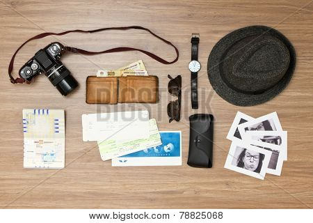 International travel background with a retro or vintage touch. Items include an old photo camera, passport, wallet with currency, airplane ticket, hat, sunglasses and black and white photos