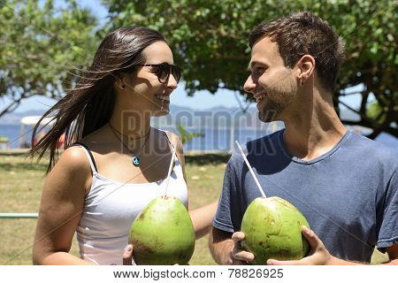 Happy couple drinking coconut water