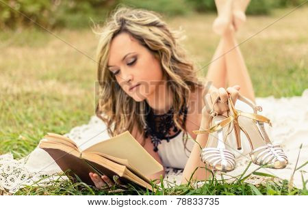 Romantic girl with shoes in the hand reading a book outdoors