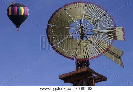 Green windmill with black hot air balloon