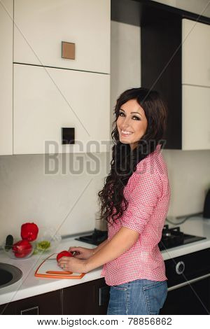 Young woman preparing a salad in the kitchen.