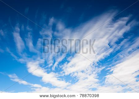 Dramatic blue sky background with streaky clouds