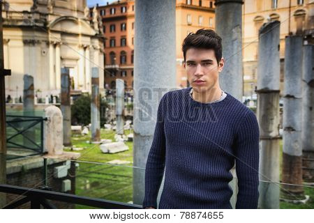 Young Man In Rome Standing In Front Of Foro Traiano And Fori Imperiali