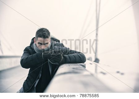 Well dressed handsome young detective or policeman or mobster standing in an urban environment aiming a firearm hiding behind small wall with a determined expression side view poster