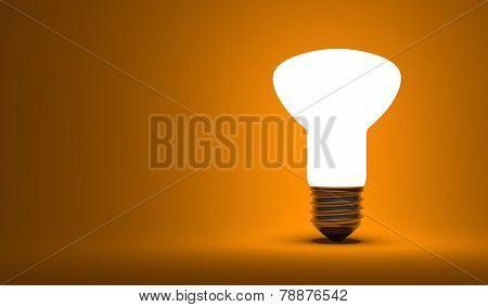 Shining Ellipsoidal Light Bulb On Orange