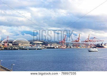 Port cranes and buildings under blue cloudy sky in Seattle downtown.
