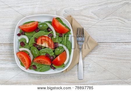 Fresh Salad On White Plate With Fork And Napkin