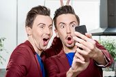 Friendly brothers twins having fun taking selfie photo with smart phone in the white home or restaurant interior poster