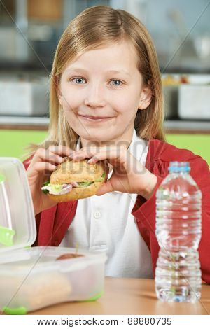 Girl Sitting At Table In School Cafeteria Eating Healthy Packed