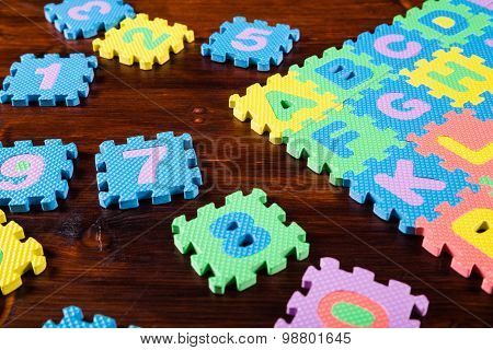 colorful puzzle letters on wooden background
