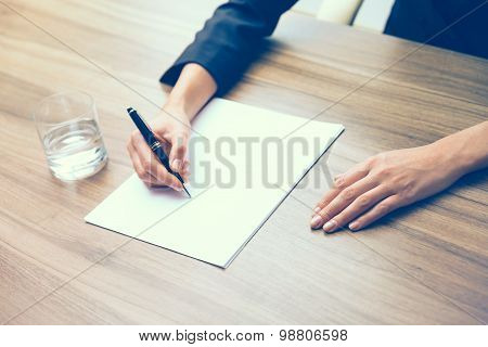 Closeup Of A Business Woman's Hands While Writing Down Some Essential Information. A Glass Of Water,