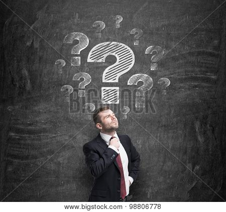 Thoughtful Businessman Is Trying To Find A Proper Solution. Question Marks Are Drawn On The Black Ch