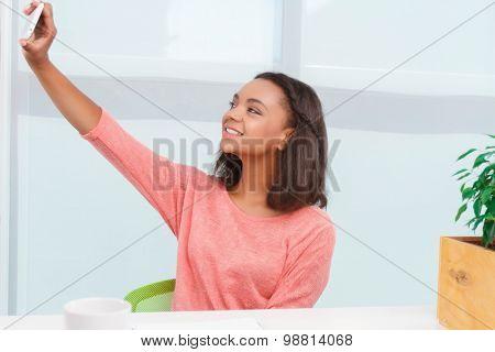 Pretty mulatto woman doing selfie