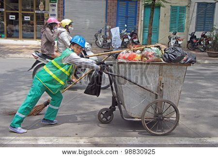 street cleaner is wheeling trolley with garbage in Hanoi