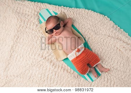 Newborn Baby Boy Sleeping On A Surfboard
