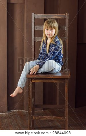 Girl 6 Years Old  Jeans And A Blue Shirt Is Sitting On High Chair In  Room