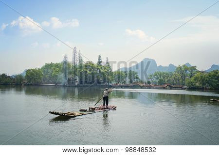 Old lady paddling a bamboo raft