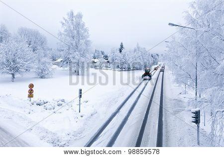 Midwinter traffic on snowy streets, roads.