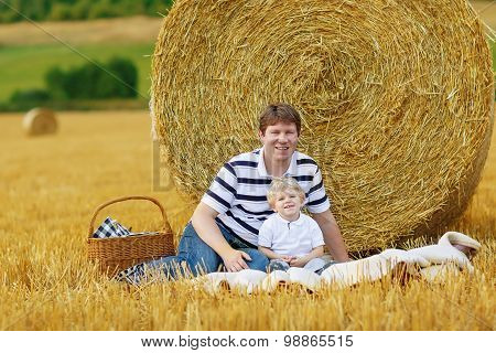 Young ather and little son kid boy having picnic on yellow hay field in summer outdoors. Family having fun together. poster